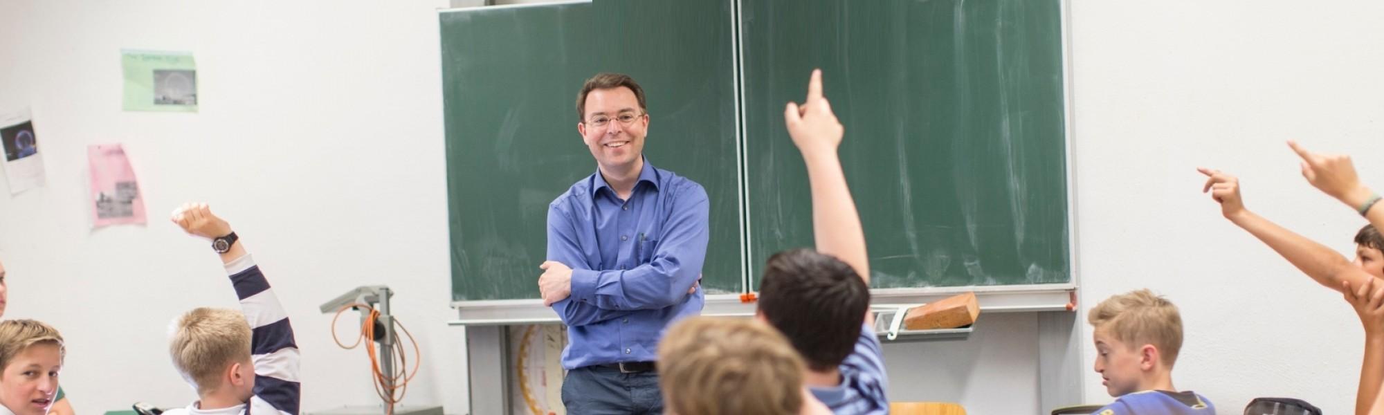 Wer hat eine Frage? Unterrichts-Situation mit Pater Modemann.
